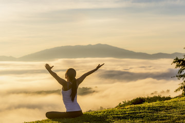 Woman with arms raised sitting on mountain by cloudscape