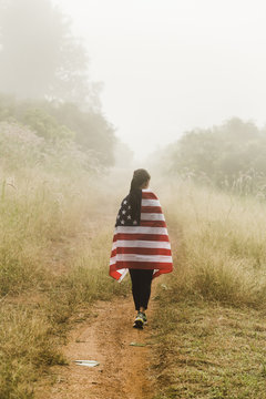 Rear view of woman with American flag walking on dirt road in forest
