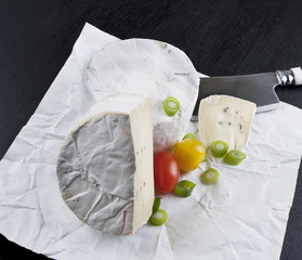 Soft cheese on white wrapping paper and black table