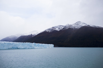 Scenic view of glaciers in lake by mountain against cloudy sky