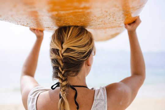 Rear view of woman carrying surfboard on head at beach