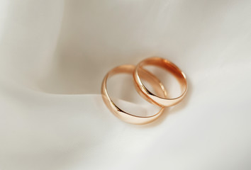 gold wedding rings lying on white satin