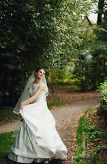 wonderful young bride dances in a green garden