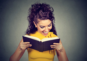 Happy young woman reading a book