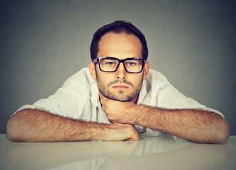 Bored man daydreaming showing no interest sitting at table