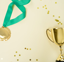 gold medal and cup on yellow background
