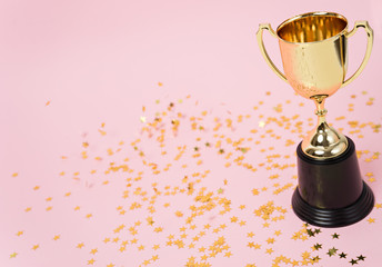 gold winner cup on pink background