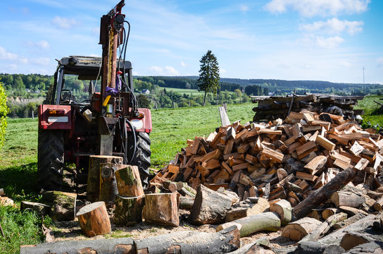 Tractor with log splitter next to pile of firewood