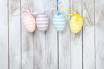 Pastel colored easter eggs over rustic wooden background.