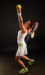 Tennis player serving a ball.Studio shot on dark background.