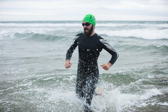 Athlete in wet suit running