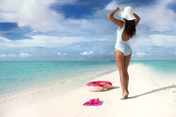 White sand tropical beach and woman wearing hat and swimsuit. Summer fun travel holiday concept
