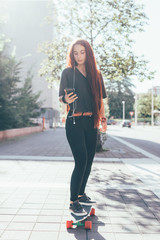 Young woman skater using smart phone music