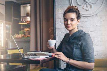 Young businesswoman sitting at table in cafe, drinking coffee and looking at camera.On table is laptop, mobile phone and notebook. Girl waiting for friends, blogging.Freelancer working outside office.