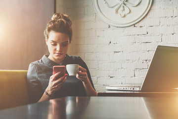 Young woman sitting in cafe at table, drinking coffee and using smartphone. On table is laptop. On background white brick wall. Student learning online. Girl shopping online, checking email, chatting.