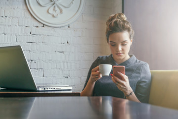 Young businesswoman sitting in cafe at table, drinking coffee and using smartphone. On table is laptop. On background white brick wall. Student learning online. Girl shopping online, checking email.