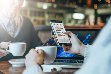 Close-up of a smartphone in female's hand. Graphs and charts on smartphone screen.Two young business women sitting at table,drinking coffee and analyzing data.On table laptop.Students studying online.