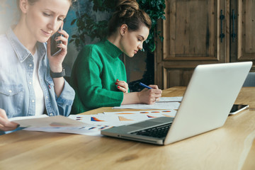 Two young business women sitting in office at table and work together.On table laptop and paper charts.First woman signs documents,second looking charts and talking on phone. Students learning online.