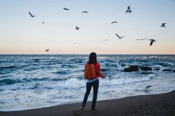 Young happy girl with orange backpack feeding seagulls ocean