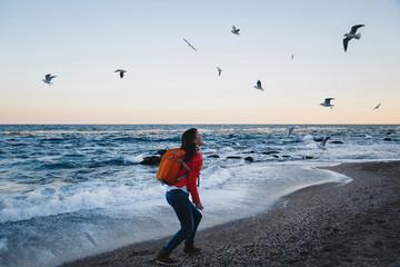 Young happy girl with orange backpack feeding seagulls sea