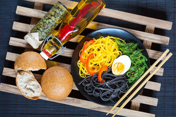 Hiyashi wakame with sesame and nut sauce, black and corn noodles, boiled egg. Bottle of olive oil with chili pepper, black olives and capers in jar, bran bread. The rustic wooden lattice, black makisu