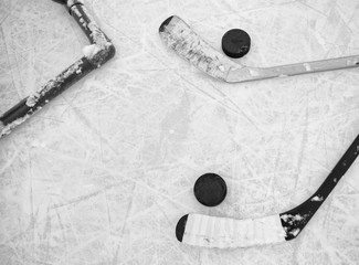 Two hockey sticks and pucks laying on textured ice skating rink in black and white