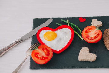valentine day.romantic breakfast. fried egg, bread and vegetables on wooden tray