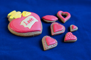Composition of heart shaped honey cakes on blue background