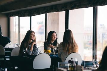 girls having fun out in town at favorite restaurant, talking, sh