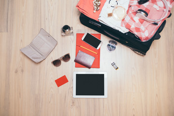 Open traveler's bag with women clothing, accessories, credit cards, sun glasses and smart phone. Travel and vacations concept.