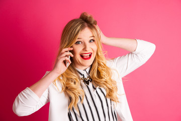 excited blonde teenage girl talking on smart phone over pink bac