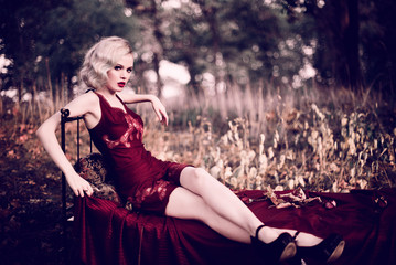 Beautiful and elegant blonde woman with red lips and hair waves wearing wine red nightie posing on the bed outdoors autumn, retro vintage style and fashion. Retouched toning shot
