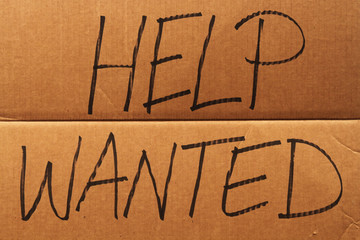 "The words ""Help Wanted"" written on a cardboard sign"