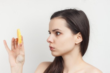 woman looking at sponge, side view