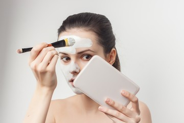 woman makes a face mask and a mirror in her hand