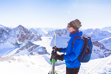 Skier standing with ski in hand enjoying Alps mountains landscape