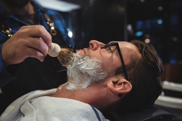 Mid section of barber applying cream on clients beard