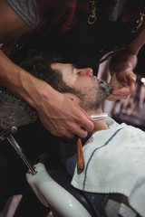 Man getting his beard shaved with razor