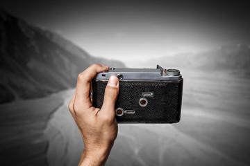 Man taking photo with vintage camera . Mixed media