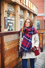 Girl near cafe with garland winter street style