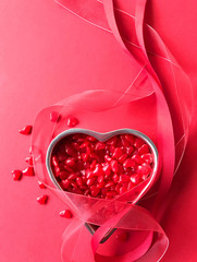 Valentine hard candies in a heart-shaped tin with ribbons and copy space