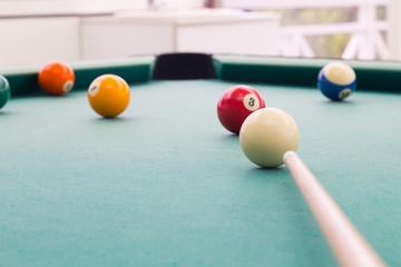 Cue aiming red ball into snooker billards table pocket