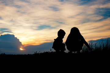 Silhouette, group of happy children playing on meadow, sunset, r