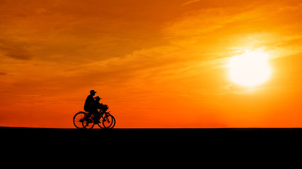 Image of sporty couple on bicycles outdoors against sunset. Silh