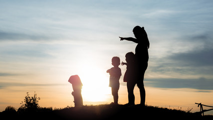 woman and her son and daughter watching sunset