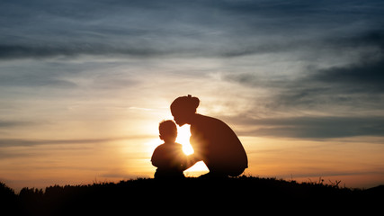 Silhouette of a young mother lovingly kissing her little child o