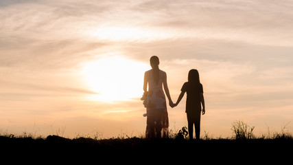 Silhouette of woman and her sister holding hands at sunset