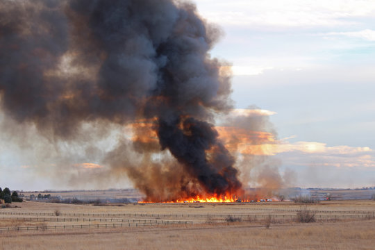 A wildfire in Colorado produces a plume of black smoke rising into the sky.