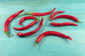 Red hot chili peppers on vibrant turquoise texture