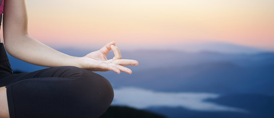 close up and selective focus on fingers of asian woman in yoga over blurred sunset backgrounds : asian woman in yoga pattern exercise for healthy life :concentrate woman yoga concept.